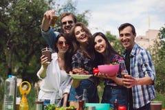 Groupe d'amis ayant le pique-nique dans le parc Image libre de droits