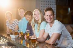Groupe d'amis ayant le verre de bière au compteur de barre Photographie stock libre de droits