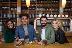 Groupe d'amis ayant le verre de bière et de nourriture mexicaine dans la barre Photos stock