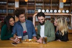 Groupe d'amis ayant le verre de bière et de nourriture mexicaine dans la barre Photo libre de droits