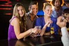 Groupe d'amis ayant le verre du cocktail au compteur de barre Photos stock