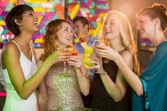 Groupe d'amis ayant le verre du cocktail dans la barre Photo libre de droits