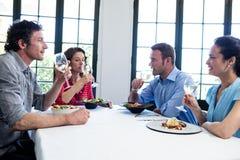Groupe d'amis ayant le vin dans un restaurant Image libre de droits