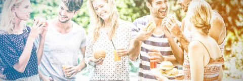 Groupe d'amis ayant les hamburgers et le jus image libre de droits