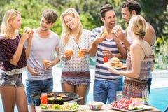 Groupe d'amis ayant les hamburgers et le jus Photo libre de droits