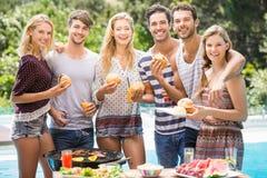 Groupe d'amis ayant les hamburgers et le jus Photographie stock libre de droits