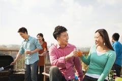 Groupe d'amis ayant un barbecue sur un dessus de toit Images stock