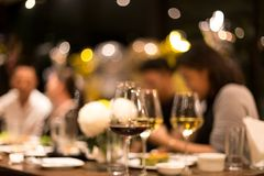 Groupe d'amis ayant un dîner et un vin dans le conceptaul brouillé Images stock