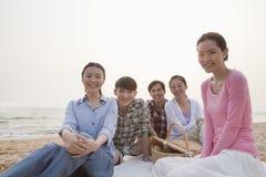 Groupe d'amis ayant un pique-nique par la mer Photo stock