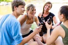 Groupe d'amis buvant de la bière au lac Photo stock