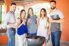 Groupe d'amis buvant de la bière dans un barbecue Photo stock