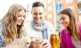 Groupe d'amis buvant de la bière dans une barre Photos libres de droits