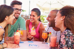 Groupe d'amis buvant des cocktails à la barre extérieure Images stock