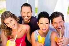Groupe d'amis buvant des cocktails dans la barre de plage Images libres de droits