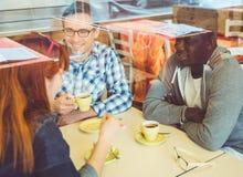 Groupe d'amis buvant du café dans une barre Images libres de droits