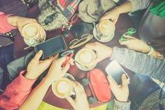 Groupe d'amis buvant du cappuccino au restaurant de café Images stock