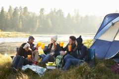 Groupe d'amis buvant en dehors de leur tente près d'un lac Image libre de droits