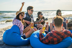 Groupe d'amis buvant sur la partie de plage Photographie stock libre de droits