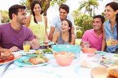 Groupe d'amis célébrant appréciant le repas dans le jardin à la maison Images libres de droits