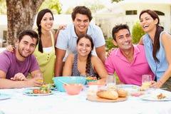 Groupe d'amis célébrant appréciant le repas dans le jardin à la maison Photos stock