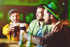 Groupe d'amis célébrant au bar irlandais Photographie stock libre de droits