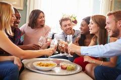 Groupe d'amis célébrant avec du pain grillé à la maison Image stock