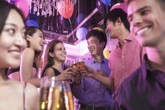 Groupe d'amis célébrant, grillant avec le champagne, boîte de nuit dans Pékin Photo libre de droits