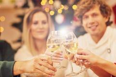 Groupe d'amis célébrant Noël à la maison Photographie stock