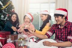 Groupe d'amis célébrant Noël à la maison et le grillage de chapeaux Photos libres de droits