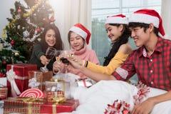 Groupe d'amis célébrant Noël à la maison et le grillage de chapeaux Images libres de droits