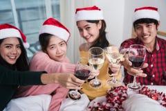 Groupe d'amis célébrant Noël à la maison et le grillage de chapeaux Photo libre de droits