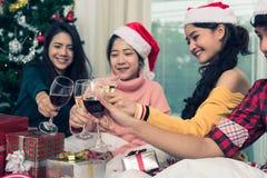 Groupe d'amis célébrant Noël à la maison et le grillage de chapeaux Photographie stock libre de droits