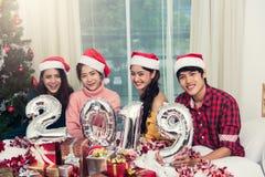 Groupe d'amis célébrant Noël à la maison et montrant 2019 Photographie stock libre de droits