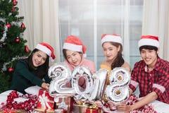 Groupe d'amis célébrant Noël à la maison et montrant 2018 Photographie stock libre de droits