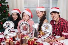 Groupe d'amis célébrant Noël à la maison et montrant 2019 Image libre de droits