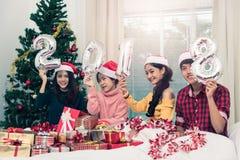 Groupe d'amis célébrant Noël à la maison et montrant 2018  Photo stock