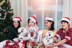 Groupe d'amis célébrant Noël à la maison et montrant 2018 Images stock
