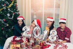 Groupe d'amis célébrant Noël à la maison et montrant 2018 Image libre de droits