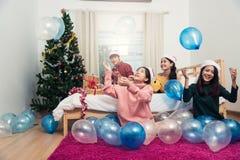 Groupe d'amis célébrant Noël à la maison jetant le ballon Photos libres de droits