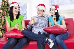 Groupe d'amis célébrant un réveillon de Noël Photographie stock