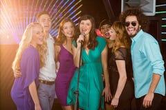 Groupe d'amis chantant la chanson ensemble dans la barre Images libres de droits