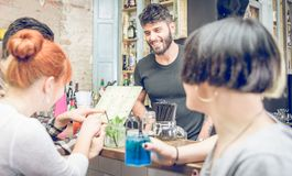 Groupe d'amis choisissant le cocktail du menu dans une barre Photos stock