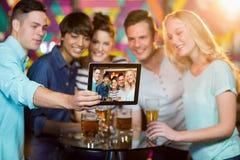 Groupe d'amis cliquant sur une photo de comprimé numérique Image stock