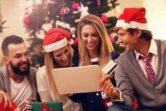 Groupe d'amis commandant des cadeaux de Noël en ligne Photographie stock libre de droits