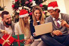 Groupe d'amis commandant des cadeaux de Noël en ligne Photos libres de droits