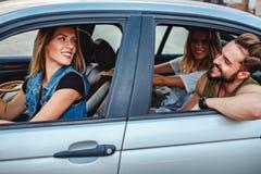 Groupe d'amis conduisant dans la voiture et le sourire Image libre de droits