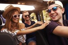 Groupe d'amis conduisant la voiture à couvercle serti sur la route de campagne Photo libre de droits