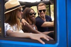 Groupe d'amis conduisant la voiture à couvercle serti sur la route de campagne Photo stock