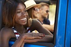 Groupe d'amis conduisant la voiture à couvercle serti sur la route de campagne Photographie stock