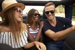 Groupe d'amis conduisant la voiture à couvercle serti sur la route de campagne Image libre de droits